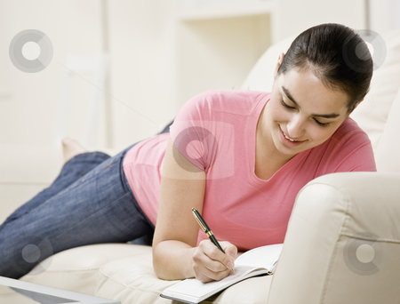 Young Woman Writing in Journal stock photo, Young woman lying on couch and writing in journal. Horizontally framed shot. by Jonathan Ross