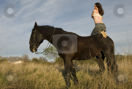 Sexy woman on horse stock photo, Happy girl and her black stallion in a field by Bonzami Emmanuelle
