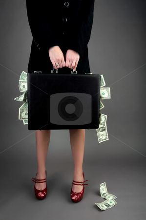 Woman holding briefcase overflowing with money stock photo, Image of a woman, from shoulders down, holding a black briefcase overflowing with money by Greg Blomberg
