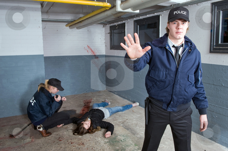 Back away stock photo, Police officer keeping bystanders at a distance from a crime scene with a murdered woman in the background by Corepics VOF