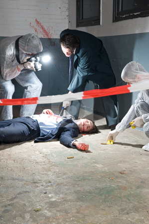Crime Scene Investigation stock photo, Murder scene with two forensic analysts and a police lieutenant investigating a crime on a businessman in a basement by Corepics VOF
