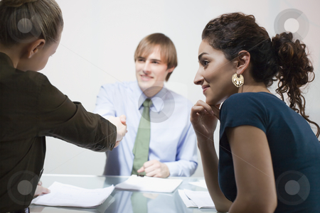Three Businesspeople in Meeting stock photo, Three businesspeople in meeting. A male and female are shaking hands. Horizontally framed shot. by Sean De Burca
