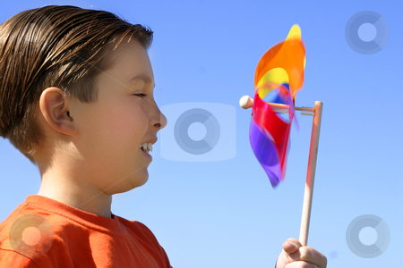 Boy with a spinning wheel pinwheel stock photo, Childs amusement watching a spinning pinwheel toy closeup by Leah-Anne Thompson