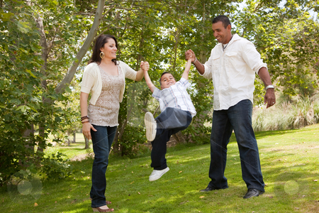 Young Hispanic Family Having Fun in the Park stock photo, Hispanic Man, Woman and Child having fun in the park. by Andy Dean