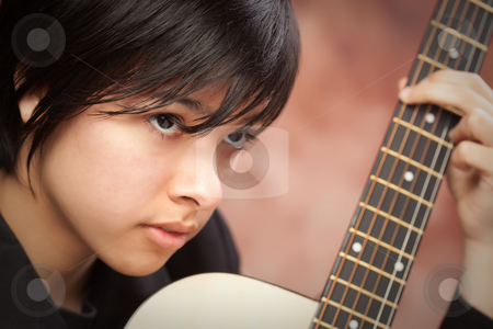 Attractive Ethnic Girl Plays Guitar stock photo, Attractive Ethnic Girl Enjoys Playing Her Guitar. by Andy Dean