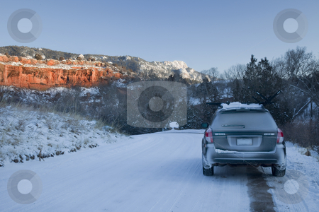 Winter driving in Colorado stock photo, Passenger car and snow covered road in Colorado backcountry with red sandstone cliffs and Horsetooth Rock near Fort Collins in sunset light by Marek Uliasz