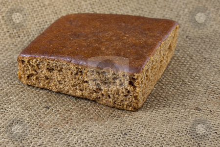 Gingerbread cake stock photo, A piece of gingerbread cake on burlap canvas by Marek Uliasz