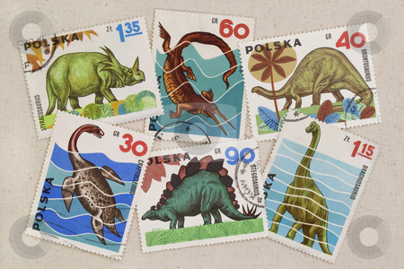 Dinosaurus - set of vintage post stamps from Poland stock photo, A variety of dinosaur species on vintage canceled post stamps from Poland placed casually on artist cotton canvas by Marek Uliasz