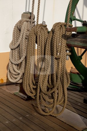 Coiled ropes and winch stock photo, Three coils of rope on a deck of sailing ship next to winch used rise sails by Marek Uliasz