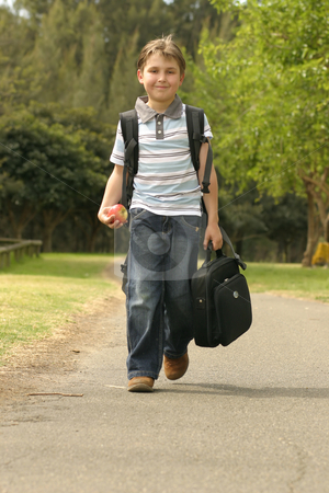 Back to School stock photo, Boy walking to school.  He has a backpack, carrying a small portable computer and is holding an apple in his hand by Leah-Anne Thompson