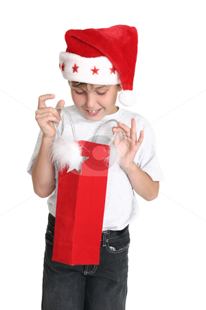 Opening a Christmas Gift stock photo, A delighted young boy looks inside a gift bag by Leah-Anne Thompson