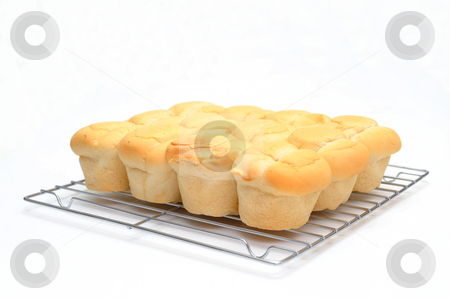 Dinner Roll stock photo, Brown and serve dinner rolls on a wire bakers cooling rack by Lynn Bendickson