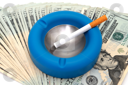Cost Of Smoking stock photo, An un-lit cigarette in a blue and silver ashtray on top of fanned out United States twenty dollar bills portraying the high cost of smoking by Lynn Bendickson
