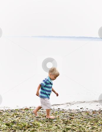 Boy walking near ocean at beach stock photo, Boy walking near ocean at beach by Jonathan Ross