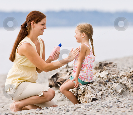 Mother applying sunscreen to daughter at beach stock photo, Mother applying sunscreen to daughter at beach by Jonathan Ross