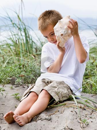 Boy listening to seashell at beach stock photo, Boy listening to seashell at beach by Jonathan Ross