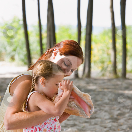 Mother watching daughter blow into seashell stock photo, Mother watching daughter blow into seashell by Jonathan Ross