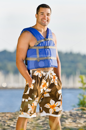 Man wearing life jacket at beach stock photo, Man wearing life jacket at beach by Jonathan Ross