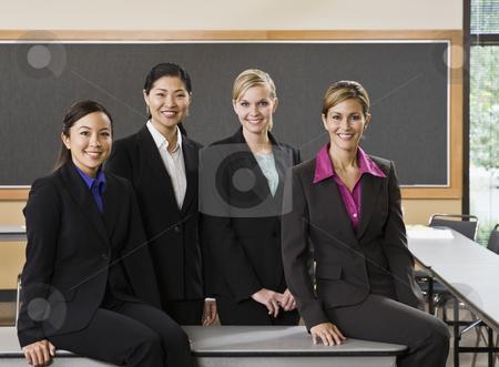Businesswomen Smiling stock photo, Businesswomen smiling, standing and sitting.  Horizontally framed shot. by Jonathan Ross