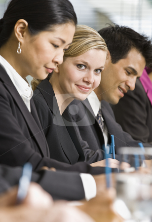 Businesswoman at Meeting Smiling stock photo, Businesswoman at meeting smiling.  Vertically framed shot. by Jonathan Ross