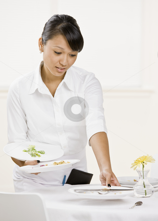 Female Server stock photo, Young female server clearing table. Vertically framed shot. by Jonathan Ross