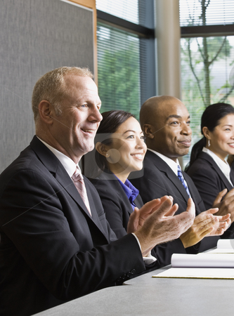 Business People in Meeting stock photo, Business people smiling in meeting applauding.  Vertically framed shot. by Jonathan Ross