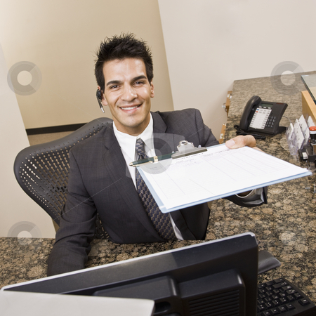 Young man Holding Clipboard stock photo, Man holding sign in sheet on clipboard.  Square framed shot. by Jonathan Ross