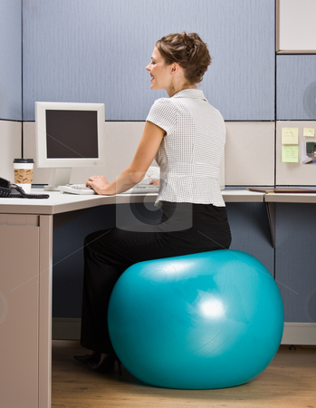 Businesswoman sitting on exercise ball at desk stock photo, Businesswoman sitting on exercise ball at desk by Jonathan Ross