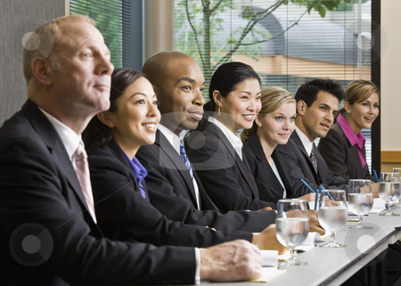 Business People in Meeting stock photo, Business people smiling in meeting.  Horizontally framed shot. by Jonathan Ross