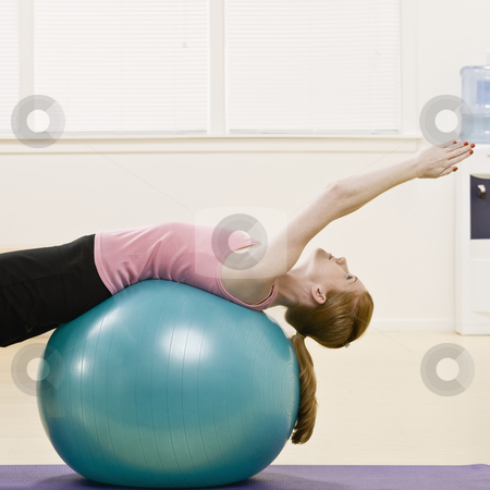 Young Woman Exercising stock photo, Young woman exercising using fitness ball. Square format. by Jonathan Ross