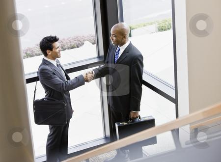Businessmen Shaking Hands stock photo, Businessmen shaking hands in front of window.  Horizontally framed shot. by Jonathan Ross