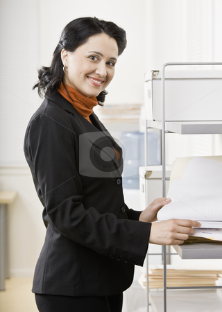 Businesswoman with Paperwork stock photo, Portrait of business woman in office. Vertically framed shot. by Jonathan Ross