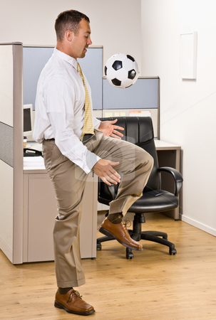 Businessman playing with soccer ball in office stock photo, Businessman playing with soccer ball in office by Jonathan Ross