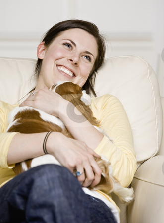 Young Woman Holding Dog stock photo, Young woman sitting on couch holding puppy. Vertically framed shot. by Jonathan Ross