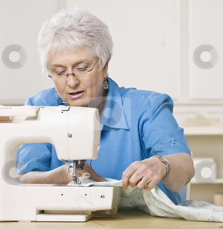 Older Woman Sewing stock photo, Older woman working on sewing machine. Square framed shot. by Jonathan Ross