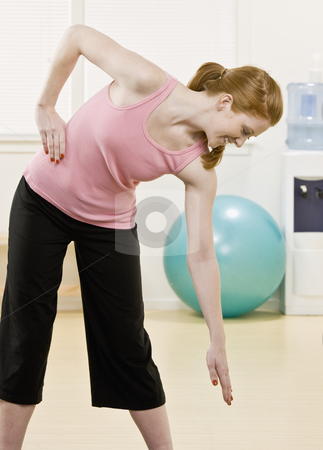 Young Woman Stretching stock photo, Young woman stretching. Vertically framed shot. by Jonathan Ross