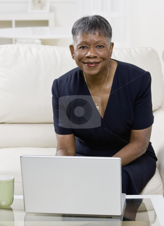 Older African American Woman Smiling stock photo, Older African American woman with laptop, smiling at camera.  Vertically framed shot. by Jonathan Ross