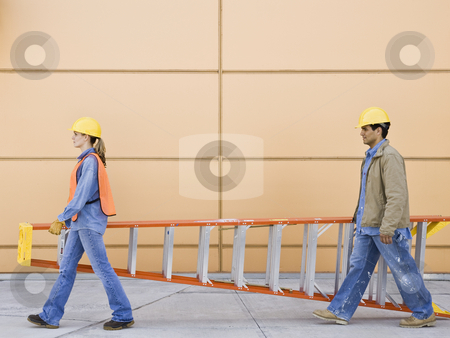 Construction Workers stock photo, Construction workers carrying orange ladder.  Horizontally framed shot. by Jonathan Ross