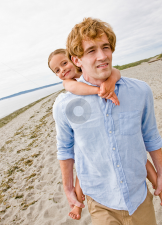 Father giving daughter piggy back ride at beach stock photo, Father giving daughter piggy back ride at beach by Jonathan Ross