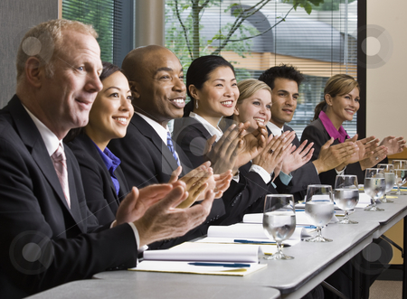 Business People in Meeting stock photo, Business people smiling in meeting applauding.  Horizontally framed shot. by Jonathan Ross