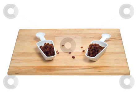 Two Scoops Of Raisins stock photo, Two scoops of raisins shot on a wooden cutting board, all isolated against a white background by Richard Nelson