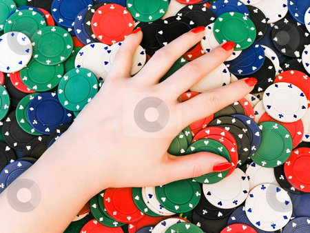 Hand at the chips stock photo, Woman hand on dispersed in casino chips by Sergej Razvodovskij
