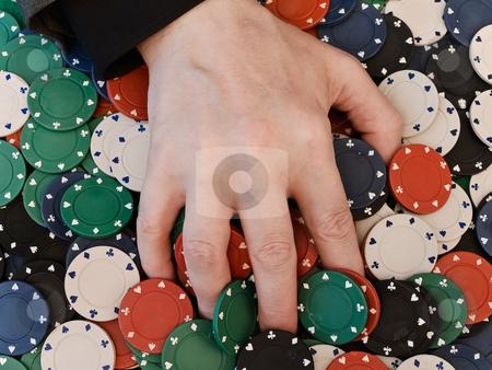 Hand at the chips stock photo, Men's hand on dispersed in casino chips by Sergej Razvodovskij