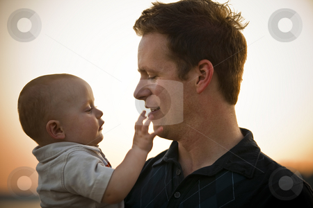 Father and Baby stock photo, Father and baby at sunset, with baby touching father's chin. Horizontal. by Keith Brofsky