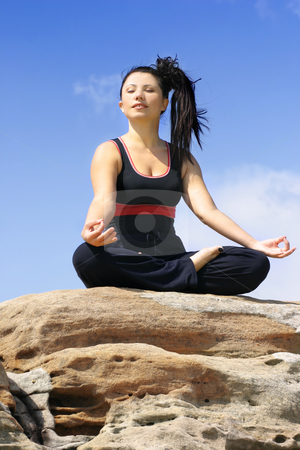 Meditation stock photo, Woman meditating on a rock with blue sky behind her. by Leah-Anne Thompson