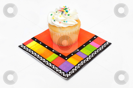 Cupcake stock photo, A single cupcake on a multi-colored party napkin isolated on a white background by Lynn Bendickson