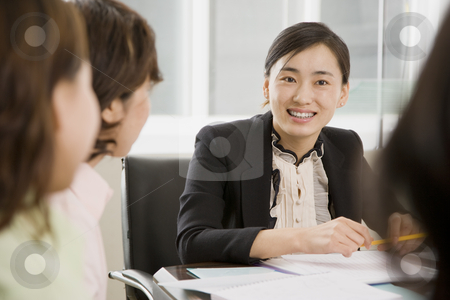Women in Business Meeting stock photo, A group of women are seated aroung a desk in a business meeting and looking at each other.  Horizontally framed shot. by Paul Burns