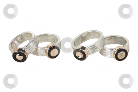 Four rings stock photo, Closeup of two pairs handiwork rings on a white background. by Roberts Ratuts