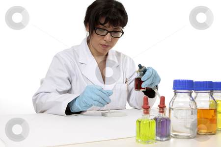 Clinical research stock photo, Scientist sitting at desk during work using a spotting plate for testing.  copyspace. by Leah-Anne Thompson
