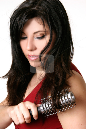 Beautiful woman brushing her hair stock photo, Haircare.  Attractive female brushing long hair with a round hair brush by Leah-Anne Thompson